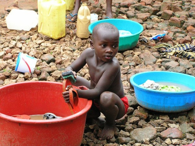 A small boy washes his shoes